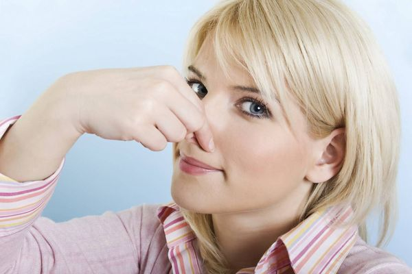 девушка закрывает нос
